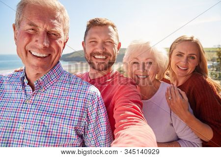 Portrait Of Senior Couple With Adult Offspring Posing For Selfie On Vacation By The Sea
