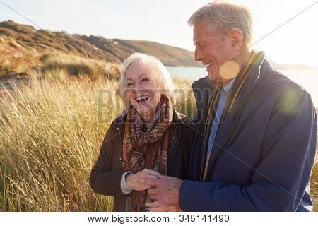 Loving Active Senior Couple Arm In Arm Walking Through Sand Dunes