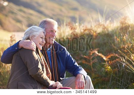 Loving Active Senior Couple Walking Along Coastal Path In Autumn Resting On Rock Together