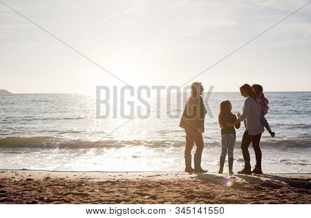 Rear View Of Grandmother With Mother And Granddaughters Standing Silhouetted By Sea