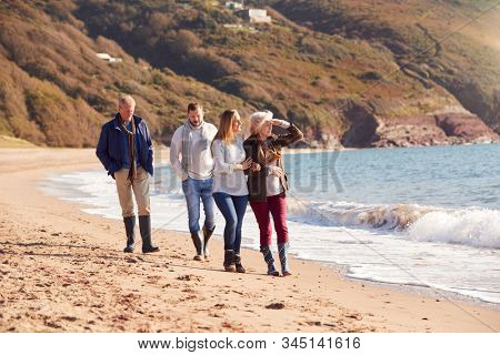 Senior Couple Walking Along Shoreline With Adult Offspring On Winter Beach Vacation