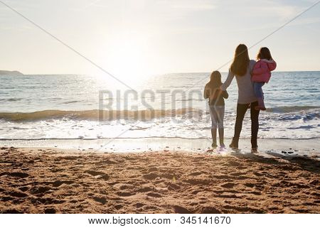 Rear View Of Mother With Daughters Looking Out To Sea Silhouetted Against Sun
