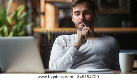 Pensive Male Thinking Over Problem Solution Working On Laptop