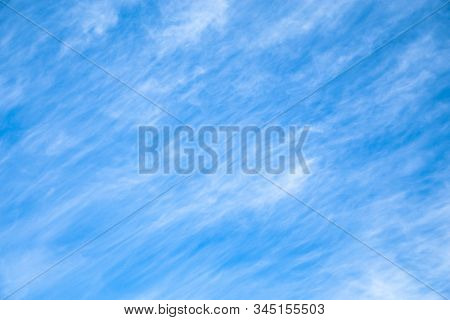 Cloudscape. Blue Sky Background With White Clouds. The Texture Of The Sky With Translucent Light Fea