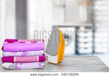 Household Laundry Ironing. Close-up Of A Yellow Electrical Iron And A Stack Of Ironed Clothes On Whi