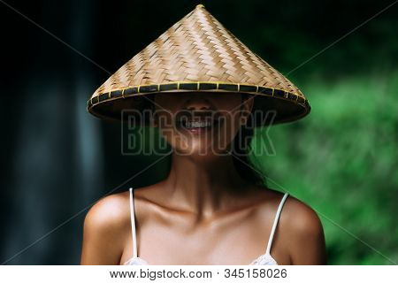 Portrait Of A Beautiful Girl In An Asian Conical Hat. Portrait Of A Smiling Girl. Beautiful Smile. C