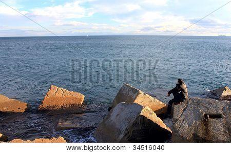 Man sitting on the big stone toward the sea.