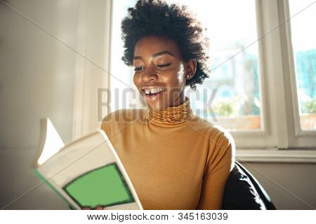 Beautiful Afro woman happily reading a book.