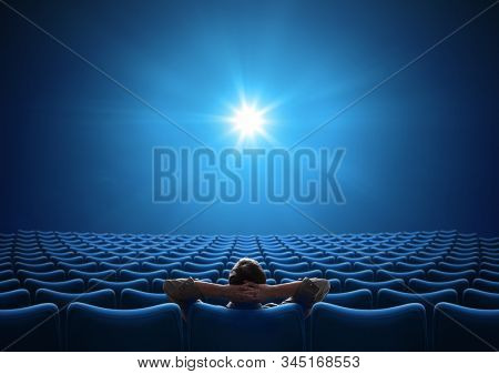Empty blue cinema with VIP sitting in center and looking on bright screen. Mixed media.