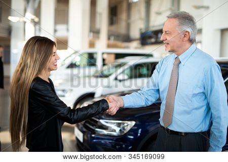 Car dealer new car concept, woman giving handshake to the car dealer to seal the deal
