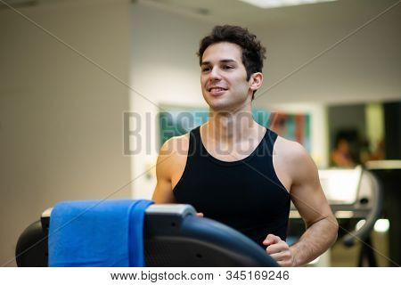 Man running on the treadmill in a gym, cardio training workout concept
