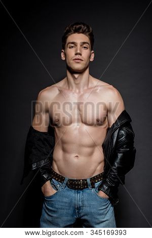 Sexy Young Man With Muscular Torso In Biker Jacket And Jeans Posing With Hands In Pockets On Black B