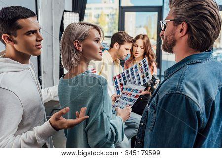 Selective Focus Of Art Director Looking At Assistant Gesturing In Photo Studio