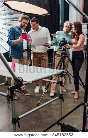 Art Director Holding Pink Shoe Near Assistant In Photo Studio