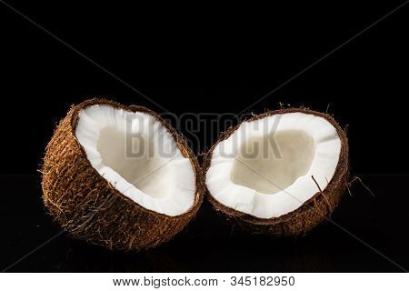 Coconut On A Black Background. Two Halves Of A Nut. Coconut Chopped In Half. White Flesh.