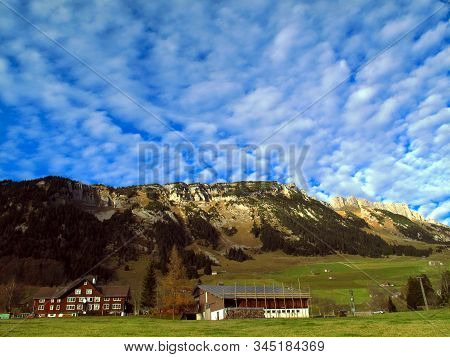 A Dramatic Cloudy Sky Over The Village Of Wildhaus In Toggenburg. Houses, Farms, Meadows, Forests, M