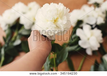 Hand Holding White Peony On Rustic Wooden Background With Stylish White Peonies. Florist Hand Arrang