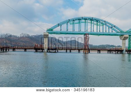 Cantilever Bridge Under Construction Over River On Cloudy Morning.