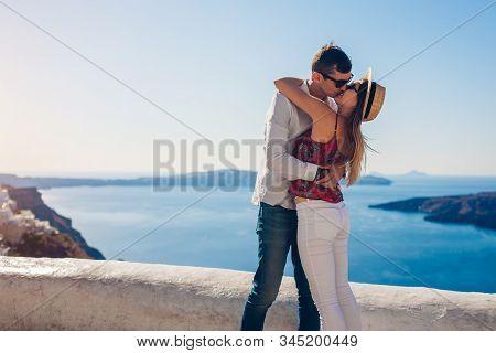 Valentines Day. Couple In Love Kissing During Honeymoon In Santorini Island, Greece. People Walking