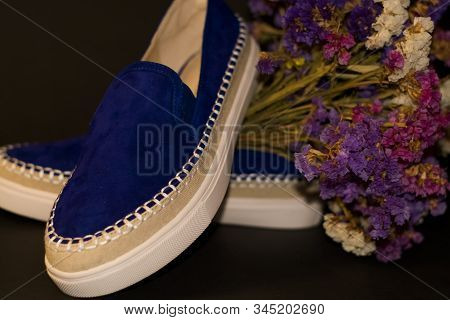 On Black Background, Pair Of Shoes, Blue Suede Slipons With White Thick Sole. Bouquet Of Dry Field F