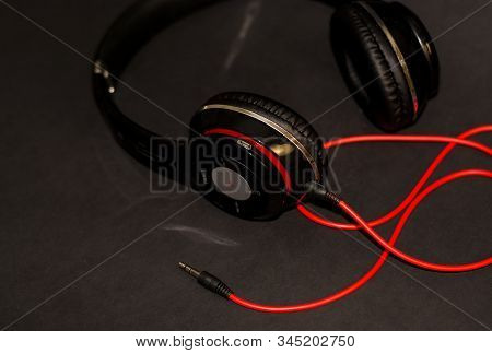 On Black Background, Large Headphones For Listening To Music With Red Elements And Cord. The Button