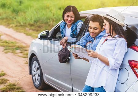 Happy Asian Woman And Her Friends Standing By Car On Coastal Road At Sunset. Young Girl Having Fun D