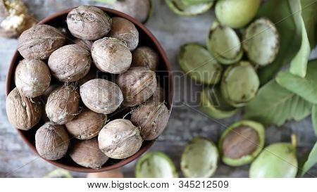 Selective Focus. Walnuts In A Bowl. Walnut Leaves Walnuts In A Green Peel. Harvest Walnuts.