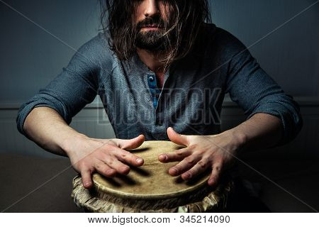 Long-haired Man Playing An Ethnic Percussion Musical Instrument Jembe. Drummer Playing African Music