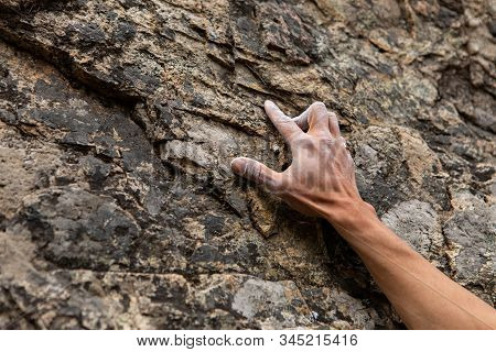 A Close Up View On The Chalked Hand Of A Traditional Rock Climber Ascending A Cliff. Reaching Upward