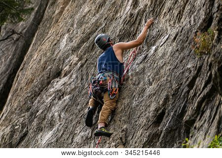 A Slim Caucasian Guy Is Seen Ascending A Sheer Rock Face During An Outdoor Adventure. Healthy Recrea