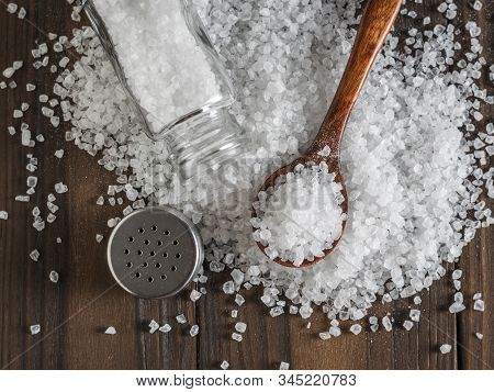 Scattered Large Sea Salt With A Wooden Spoon And Salt Shaker. Ground Stone Sea Salt.