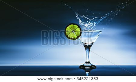 Alcohol Cocktail With Splash And Green Lime Isolated On Blue Background. Vermouth Cocktail Inside Ma