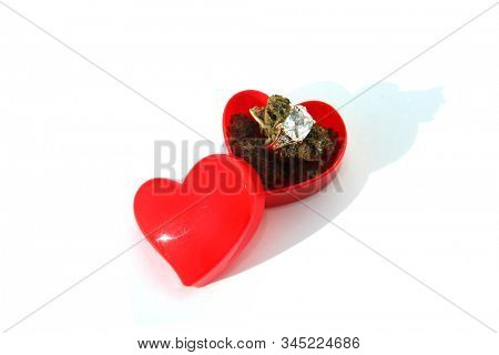 Wedding or Engagement Ring with Marijuana in a Heart Shaped Ring Box. Isolated on white. Room for text. Some people love Cannabis and Diamond Rings. Cannabis Weddings are a new trend in the USA.
