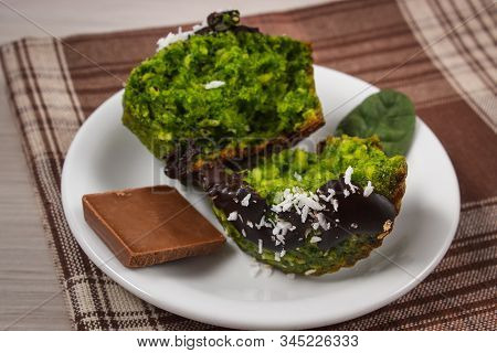 Homemade Muffins Baked With Wholemeal Flour With Spinach, Desiccated Coconut And Chocolate Glaze, De