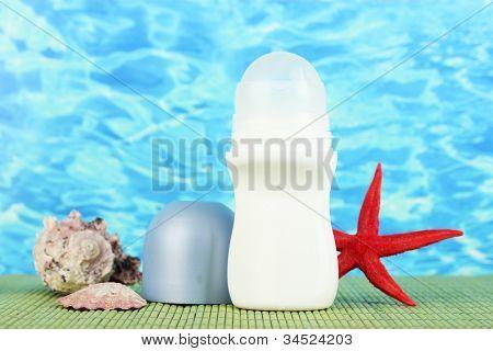 deodorant, fishstar and shells on blue sea background