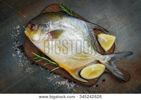 Fresh Pomfret Fish With Herbs Spices Rosemary And Lemon On Wooden Cutting Board And Black Plate Back