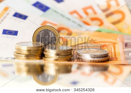 Stack Of Euro Coins On Euro Banknotes, 1 Euro Coin In Full View, For Backgrounds.