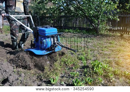 Plowing The Land In The Garden With A Cultivator. A Man Plows The Land With The Help Of Motor Cultiv