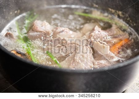 Traditional Beef Broth With Vegetable, Bones And Ingredients In Pot, Cooking Recipe. Soup In A Cooki