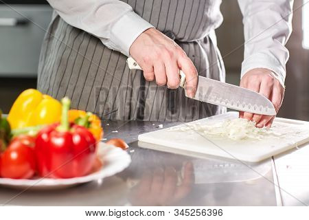 Closeup Of Hand With Knife Cutting Fresh Vegetable. Young Chef Cutting Beet On A White Cutting Board