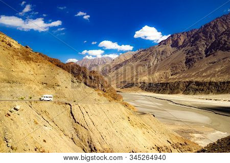 High Dynamic Range Image Of Barren Mountain In A Desert With River And Deep Blue Sky And White Patch