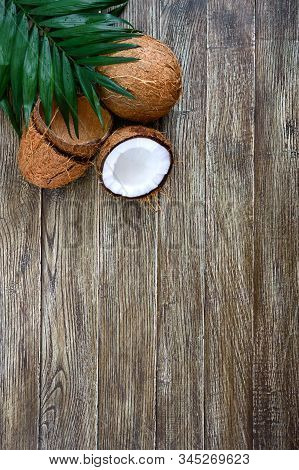 Coconut. Whole Coconut, Shell From Coconut And Green Leaves On A Wooden Background. Big Nut. Tropica