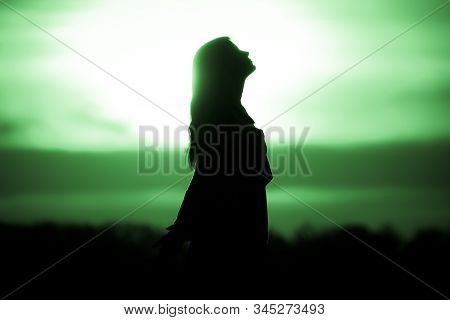 Youth Woman Soul At Green Sun Meditation Awaiting Future Times. Silhouette In Front Of Sunset Or Sun