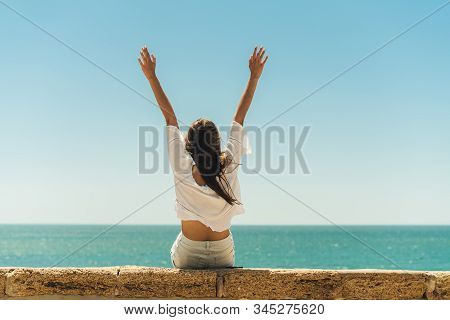The Girl Threw Up Her Hands Upright Sitting On The Parapet Against The Background Of The Ocean With