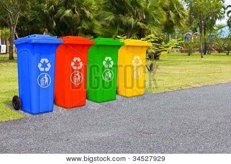 Four color trash cans (garbage bin) in the park beside the walk way poster
