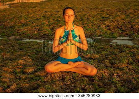 Young Woman Meditating, Practicing Yoga And Pranayama At The Beach. Sunset Yoga Practice. Hands In N