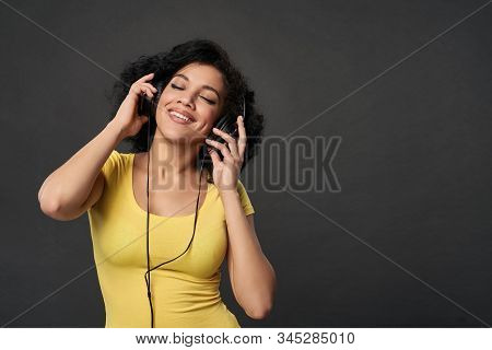 Happy Woman Listening Music In Headphones And Dancing With Closed Eyes