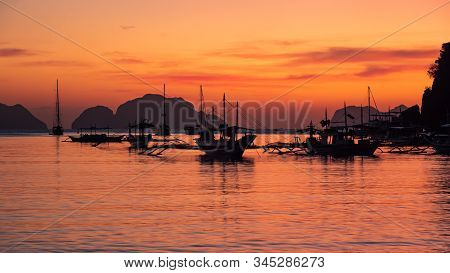 Traditional Philippine Boats Bangka At Sunset. Beautiful Sunset With Silhouettes Of Philippine Boats