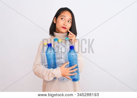 Young beautiful chinese woman recycling plastic bottles over isolated white background serious face thinking about question, very confused idea