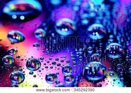 Droplets Of Water In A Vivid Colorful Blurry Background. Droplets In Abstract Colors.